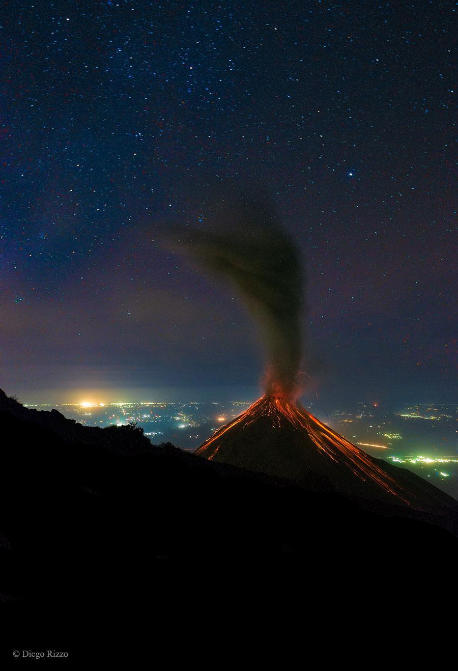Volcán de lume en erupción baixo as estrelas