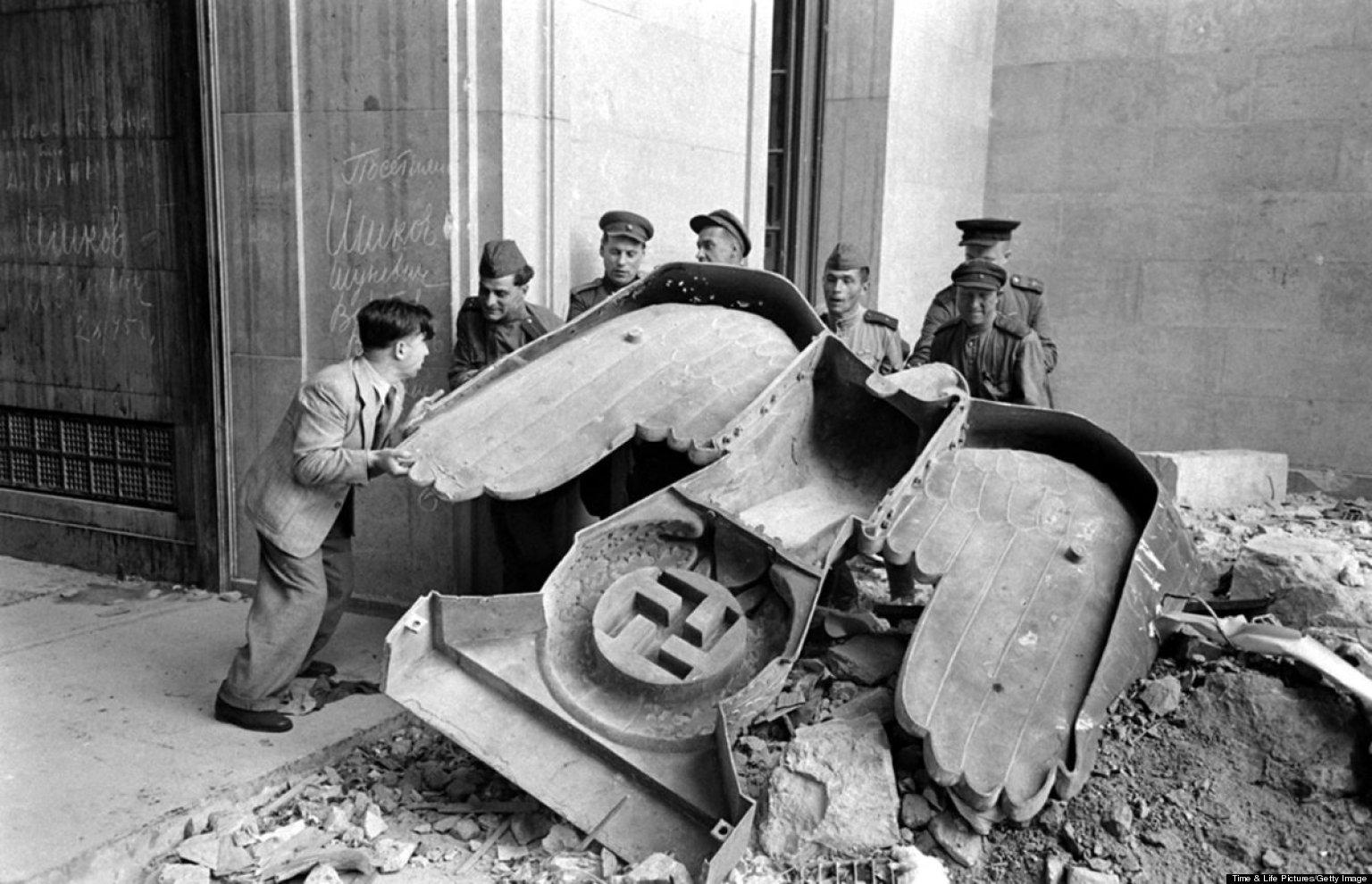 Soldados rusos desmontan un símbolo nazi en Berlín.