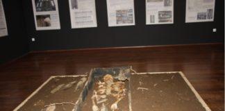 Imaxe da mostra, cun cadáver cunha botella entre as pernas, no clásico enterramento desta cadea.