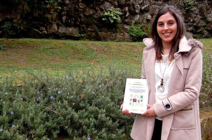 A investigadora Raquel Rodríguez coa súa tese e as herbas empregadas para o licor.