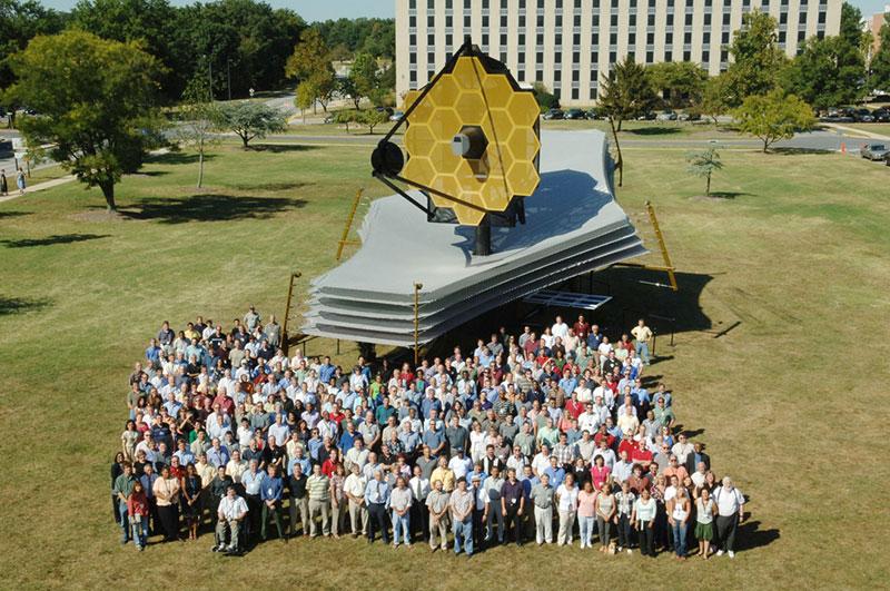 Equipo do telescopio Webb cunha maqueta do mesmo.