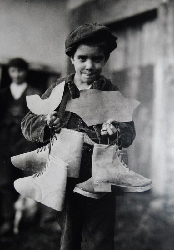 Un neno sostén varias pezas de zocos, no Outeiro (Lalín).