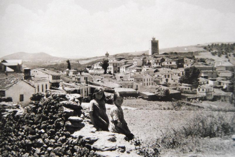 Dúas nenas miran á cámara e, ao fondo, a vila de Viana do Bolo.