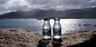 Botellas de Refix, nas rochas da Costa da Morte de onde se extrae a auga do remedio para a resaca. Imaxe: Refix.