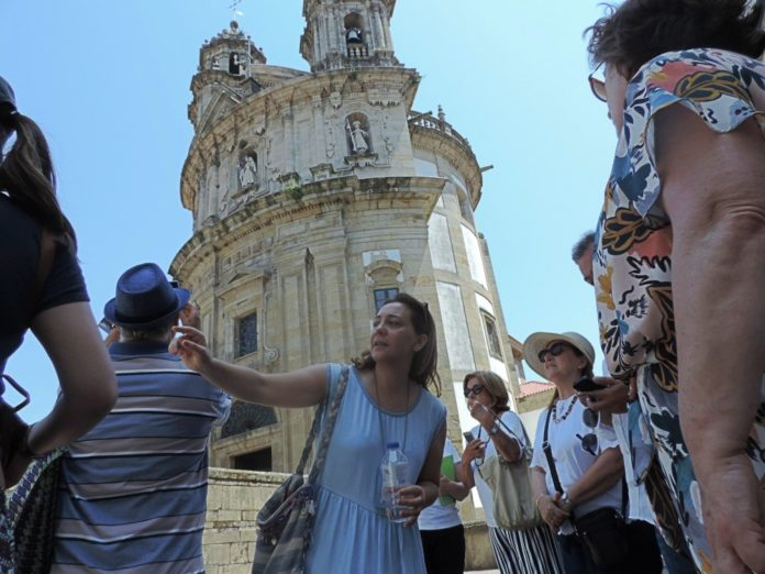 Inés Brandido e os turistas diante do Santuario da Virxe Peregrina.