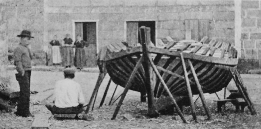 Escena da vida cotiá en Cambados; un home fala cun veciño mentres constrúe unha pequena embarcación, e ao fondo miran tres mulleres