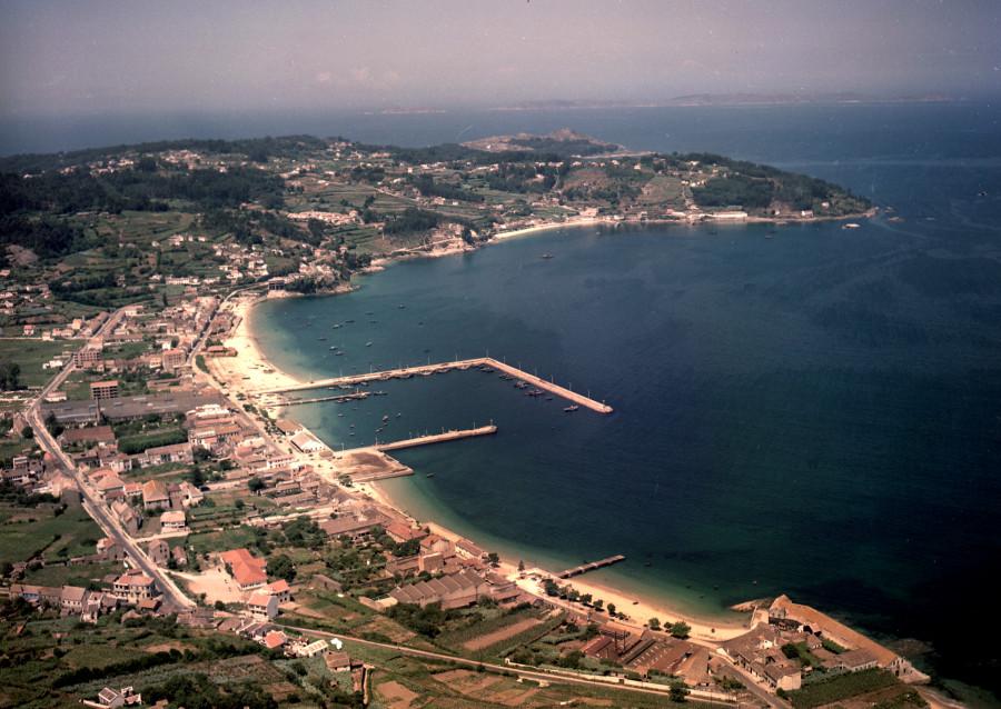 Vista aérea do núcleo urbano e porto de Bueu xunto coa costa, onde destaca o cabo Udra, os campos da contorna e, ao fondo, Ons.