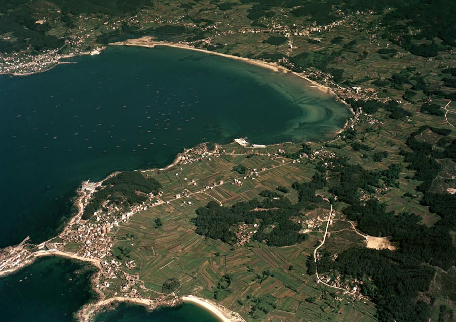 Vista aérea da enseada da Mercede e a praia de Barraña, delimitadas polos núcleos de Escarabote e Cabo de Cruz, tomada desde o lado sur. Ao fondo á dereita, núcleo de Boiro.