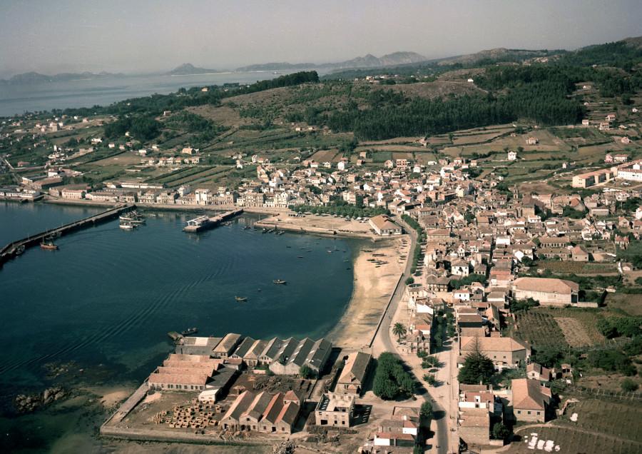 Vista aérea do núcleo urbano e o porto de Cangas cos campos da contorna e, ao fondo, as illas Cíes..