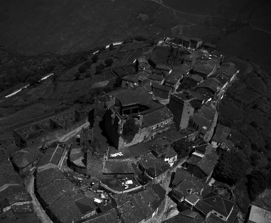 Vista aérea do castelo xunto cos edificios do núcleo urbano de Castro Caldelas e campos da contorna.