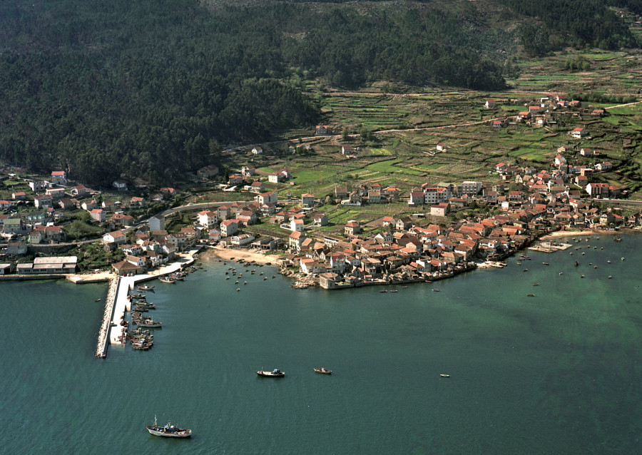 Vista aérea xeral do núcleo urbano e porto de Combarro xunto coas vivendas e campos da contorna.