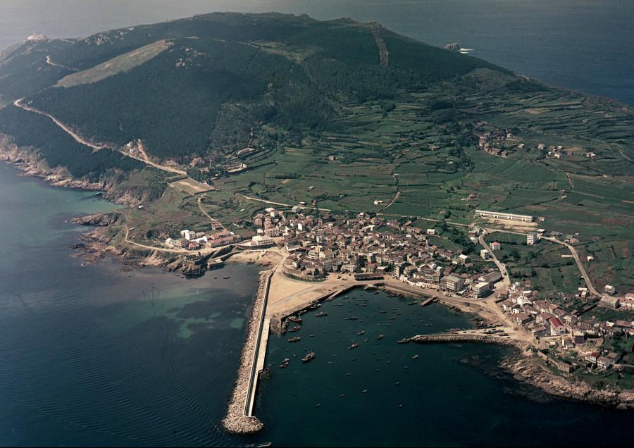 Vista aérea xeral do núcleo urbano e porto de Fisterra co cabo, o faro (arriba á esquerda) e costa da contorna.