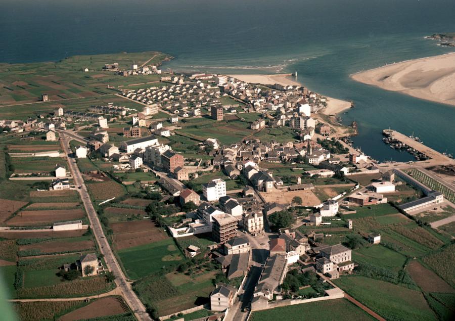 Vista aérea do núcleo urbano de Foz coa praia da Rapadoira e a entrada da ría ao fondo.