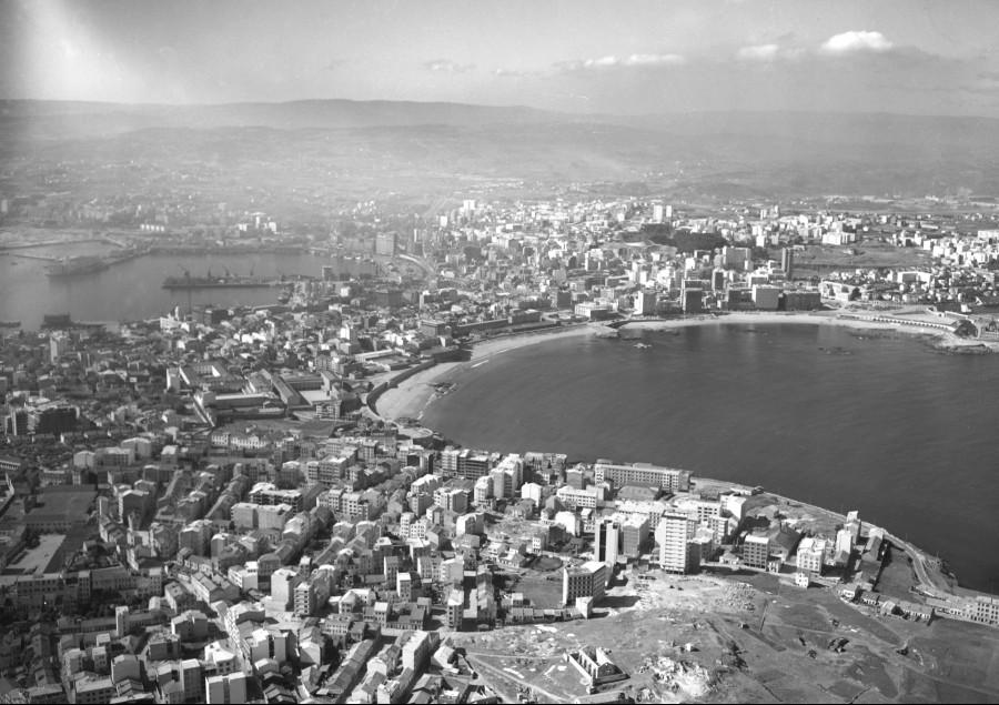 Vista xeral da cidade da Coruña co barrio de Monte Alto en primeiro termo e o porto e a enseada do Orzán enmarcado a imaxe pola esquerda e dereita respectivamente.
