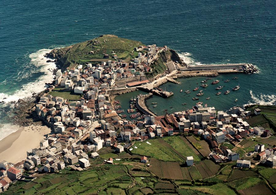 Vista aérea do núcleo urbano de Malpica, tomado desde o interior, co porto no lado dereito e a praia no esquerdo.
