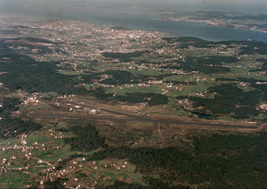 Vista aérea xeral da pista do aeroporto de Peinador cos campos da contorna e, ao fondo, a cidade e a ría de Vigo.