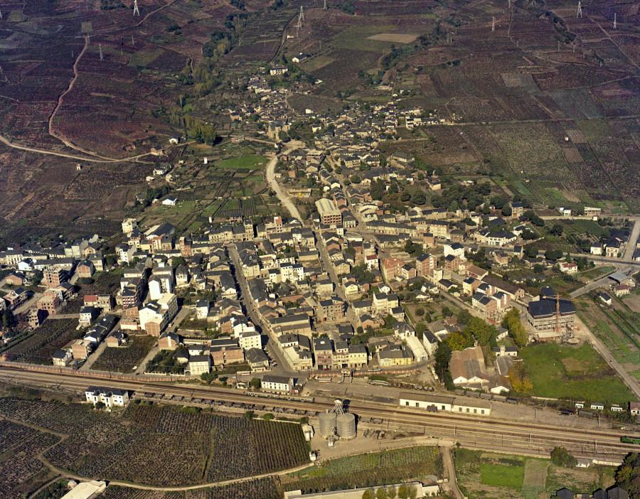 Vista aérea do núcleo urbano da Rúa coa estación de ferrocarril en primeiro termo e os campos de cultivo da contorna.