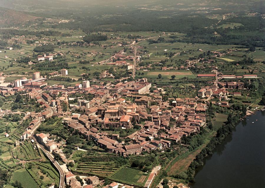 Vista aérea xeral da vila de Tui, presidida pola catedral e o núcleo histórico, cos campos da contorna e, na parte inferior esquerda da imaxe, o río Miño.